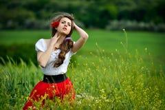Jeune belle femme sur le gisement de céréale avec des pavots en été photos libres de droits