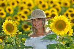 Jeune belle femme sur le gisement de floraison de tournesol en été Photo stock