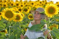 Jeune belle femme sur le gisement de floraison de tournesol en été Photos libres de droits