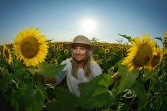 Jeune belle femme sur le gisement de floraison de tournesol en été Photo libre de droits