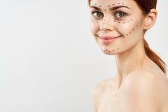 Jeune belle femme sur un fond clair avec une découpe sur le visage, chirurgie plastique, opération, l'espace vide pour la copie Image libre de droits