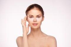 Jeune belle femme sur un fond clair, soins de la peau d'oeil, beauté, santé images libres de droits