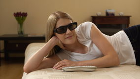 Jeune belle femme sur un mensonge de divan Met dessus les commutateurs 3d-glasses à la TV futée et observe le film 3d banque de vidéos