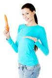 Jeune belle femme tenant la carotte fraîche. images libres de droits
