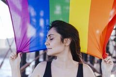 Jeune belle femme tenant un drapeau gai d'arc-en-ciel dehors MODE DE VIE un concept de fierté L'amour est amour photographie stock libre de droits