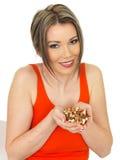 Jeune belle femme tenant une poignée d'écrous mélangés Photographie stock libre de droits