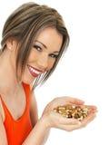 Jeune belle femme tenant une poignée d'écrous mélangés Photo libre de droits