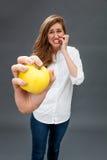 Jeune belle femme tendue rectifiant ses dents tenant une pomme Photographie stock libre de droits