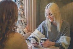 Jeune belle femme vérifiant son téléphone intelligent tout en se reposant avec son amie dans le restaurant de café Images stock