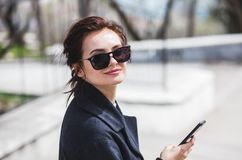 Jeune belle fille élégante de brune dans des lunettes de soleil regardant la caméra tenant son smartphone dans la rue au printemp photographie stock libre de droits