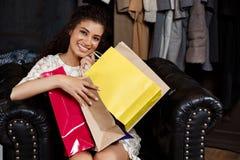 Jeune belle fille africaine s'asseyant dans le centre commercial avec des achats Image stock