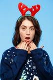 Jeune belle fille amusée de brune dans des andouillers knited de renne de chandail et de Noël souriant au-dessus du fond bleu Image libre de droits