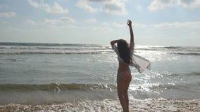 Jeune belle fille appréciant la vie et ayant l'amusement au bord de mer Femme heureuse dans le bikini et la chemise marchant sur  banque de vidéos