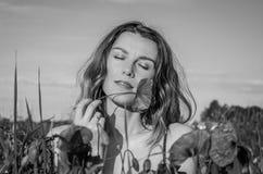 Jeune belle fille avec de longs cheveux pendant une promenade un jour ensoleillé d'été chaud au-dessus d'un champ de pavot appréc Photographie stock libre de droits