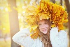 Jeune belle fille avec des feuilles d'automne dans sa main Image stock