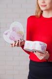 Jeune belle fille avec le cadeau de jour de valentines en BO en forme de coeur Photographie stock libre de droits