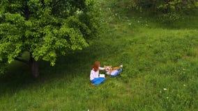 Jeune belle fille avec le chien de corgi se reposant sur une herbe sous l'arbre banque de vidéos