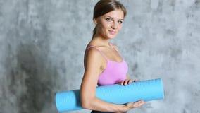 Jeune belle fille avec le sourire de tapis de yoga banque de vidéos