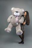 Jeune belle fille avec le sourire heureux de grand de nounours jouet mou d'ours et jouer sur le fond gris Photographie stock libre de droits