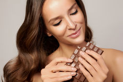 Jeune belle fille avec les cheveux bouclés foncés, les épaules nues et le cou, tenant une barre de chocolat pour apprécier le goû Photographie stock