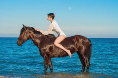 Jeune belle fille avec un cheval sur la plage images libres de droits