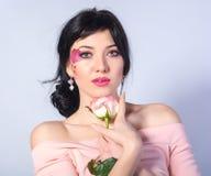 Jeune belle fille avec un coeur sur sa joue avec une rose sur a Image libre de droits