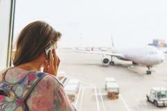 Jeune belle fille avec un sac à dos à côté des fenêtres panoramiques de l'aéroport international de terminal pour passagers Photographie stock libre de droits