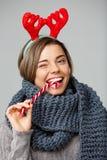 Jeune belle fille blonde dans de grands andouillers knited de renne d'écharpe et de Noël souriant mangeant le lollypop rayé Image libre de droits