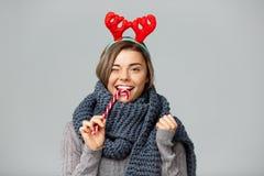 Jeune belle fille blonde dans de grands andouillers knited de renne d'écharpe et de Noël souriant mangeant le lollypop rayé Photographie stock