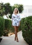 Jeune belle fille blonde posant dans la station de vacances tropicale de forêt dans le tenue décontractée blanc photo libre de droits