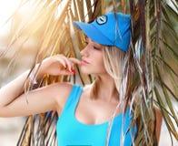 Jeune belle fille blonde posant dans la station de vacances tropicale de forêt de palmier dans le gilet et le chapeau sexy bleus  photos libres de droits