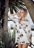 Jeune belle fille blonde posant dans la station de vacances tropicale de forêt dans la robe blanche occasionnelle avec des fleurs images libres de droits