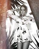 Jeune belle fille blonde posant dans la station de vacances tropicale de forêt dans la robe blanche occasionnelle avec des fleurs photographie stock