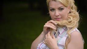 Jeune belle fille blonde posant en parc en été banque de vidéos