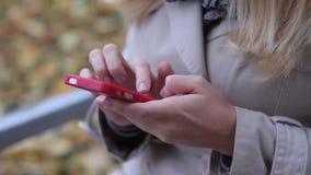 Jeune belle fille blonde s'asseyant sur un banc en parc d'automne avec un téléphone dans des mains clips vidéos