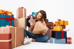 Jeune belle fille bouclée s'asseyant sur le plancher parmi des boîte-cadeau ouvrant des présents d'isolement images stock