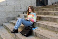 Jeune belle fille d'étudiant d'adolescent travaillant et étudiant sur l'ordinateur portable dans une ville européenne dehors photographie stock