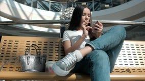 Jeune belle fille d'étudiant avec le téléphone et le café futés dans le centre commercial banque de vidéos