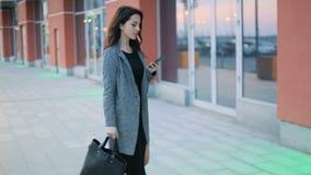 Jeune belle fille d'affaires avec le cou tatoué dans la veste grise stricte et la robe noire marchant sur la rue avec banque de vidéos