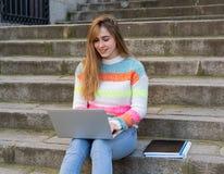 Jeune belle fille d'?tudiant d'adolescent travaillant et ?tudiant sur l'ordinateur portable dans une ville europ?enne dehors image stock