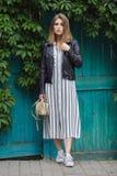 Jeune belle fille dans espadrilles rayées élégantes de blanc de robe de veste en cuir de noir de streetwear de longues et avec un Photographie stock libre de droits