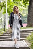 Jeune belle fille dans espadrilles rayées élégantes de blanc de robe de veste en cuir de noir de streetwear de longues et avec un Photographie stock