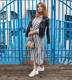 Jeune belle fille dans espadrilles rayées élégantes de blanc de robe de veste en cuir de noir de streetwear de longues et avec un Images stock