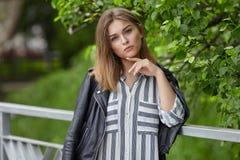 Jeune belle fille dans espadrilles rayées élégantes de blanc de robe de veste en cuir de noir de streetwear de longues et avec un Photo stock