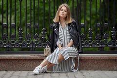 Jeune belle fille dans espadrilles rayées élégantes de blanc de robe de veste en cuir de noir de streetwear de longues et avec un Images libres de droits