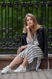 Jeune belle fille dans espadrilles rayées élégantes de blanc de robe de veste en cuir de noir de streetwear de longues et avec un Photos libres de droits