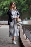 Jeune belle fille dans espadrilles rayées élégantes de blanc de robe de veste en cuir de noir de streetwear de longues et avec un Image stock