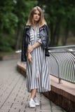 Jeune belle fille dans espadrilles rayées élégantes de blanc de robe de veste en cuir de noir de streetwear de longues et avec un Photos stock