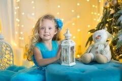 Jeune belle fille dans la robe de soirée élégante blanche bleue se reposant sur le plancher près de l'arbre de Noël et les présen photos libres de droits