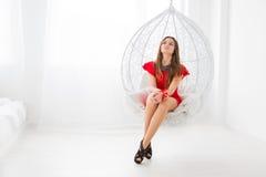 Jeune belle fille dans la robe rouge se reposant dans une oscillation décorative comme une sphère Endroit élégant et confortable  Photographie stock libre de droits